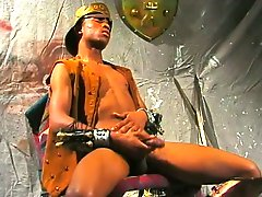 Hung black stud sits on a chair and pleases himself for the camera