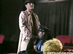 A black police woman walks into a sex theatre where a guy is talking...